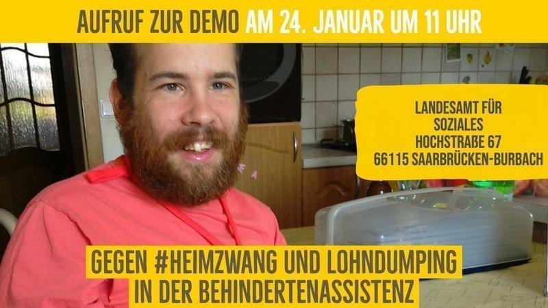 Bild zeigt einen lächelnden bärtigen Mann mit Grafiken zum Termin der Demo gegen Heimzwang. 24. Januar um 11 Uhr. Landesamt für Soziales Hochstraße 67 in 66115 Saarbrücken-Burbach